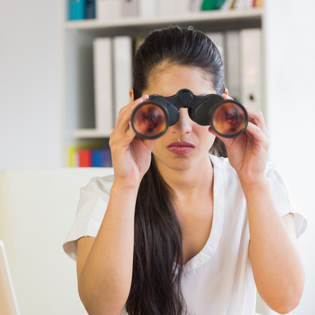 Young determined businesswoman looking through binoculars in office photo