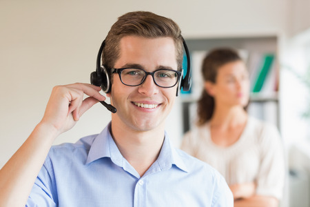 call center female: Portrait of young customer service representative wearing headset in office