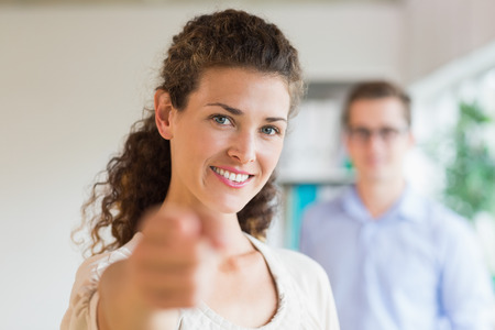 Portrait of confident businesswoman pointing while colleague standing in background at office photo