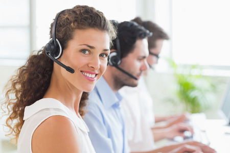 call center office: Portrait of young call center operator wearing headset with colleagues working in background at office