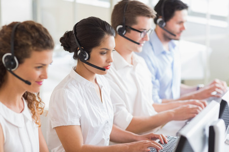 service center: Customer service operators working at desk in office