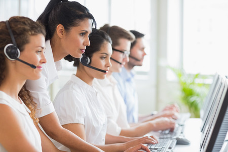 Side view of female manager assisting her staffs in a call center photo
