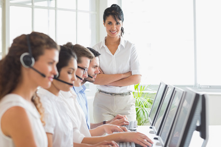 Portrait of happy female manager with business staff working in a call center photo