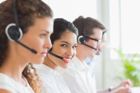 business center: Portrait of smiling businesswoman with colleagues working in call center Stock Photo