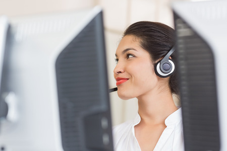 customer service representative: Female customer service representative working at computer in call center