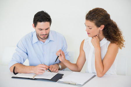 Businessman with female colleague discussing together at desk in office photo