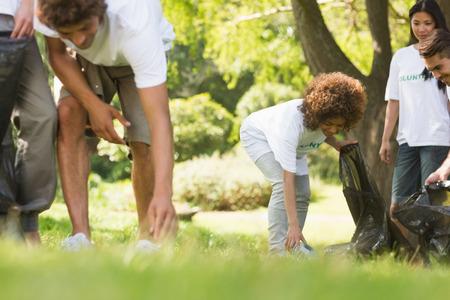 Team van jonge vrijwilligers het oppakken van zwerfvuil in het park Stockfoto