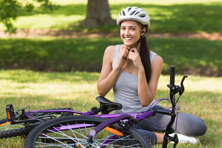 Portrait of a cheerful young woman wearing helmet besides bicycle in the park photo