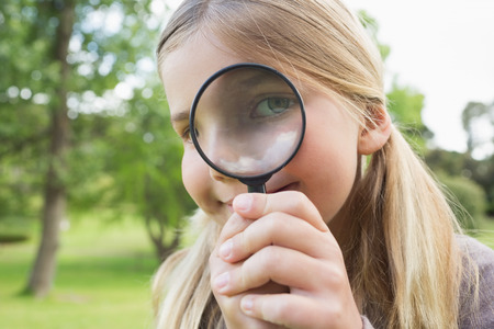 Close-up portrait of a cute young girl looking through magnifying glass at the park photo