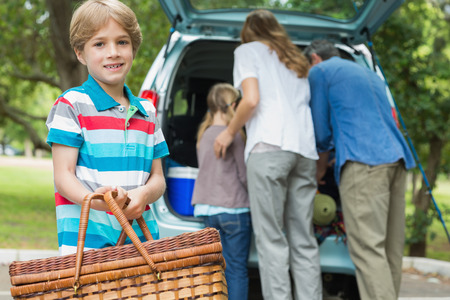 Portrait of a boy with picnic basket while family in background at car trunk photo