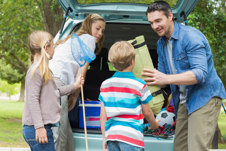 Happy family of four unloading car trunk while on picnic photo