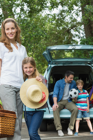 Portrait of mother and daughter with father and son sitting in car trunk photo