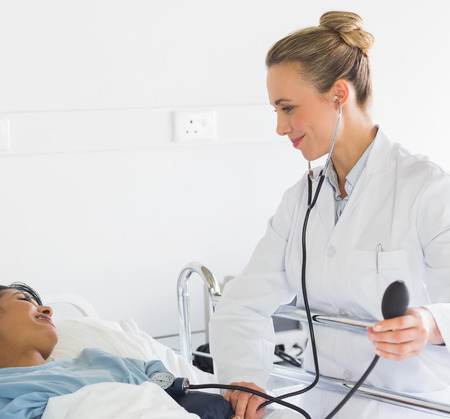 Female doctor examining patients blood pressure at hospital photo