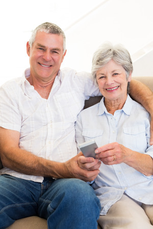 Portrait of senior couple with mobile phone at home photo
