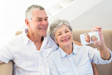 Smiling senior couple taking self portrait through smart phone at home photo