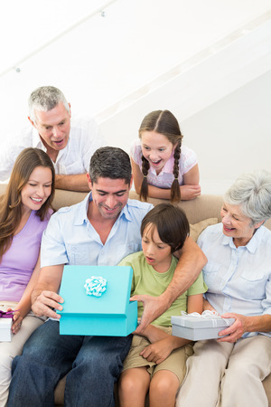 Multigeneration family gifting birthday present to man at home Stock Photo - 27117504