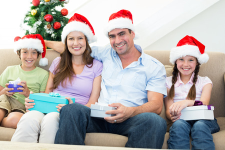 Portrait of happy family with Christmas presents at home photo