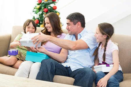 Happy family exchanging Christmas presents at home photo