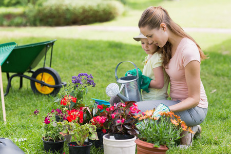 family garden: Side view of a mother and daughter engaged in gardening Stock Photo