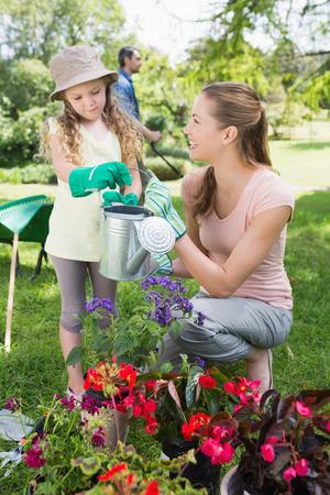regando plantas: Madre con la hija regar las plantas en el jard�n