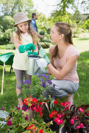 watering plants: Mother with daughter watering plants at the garden Stock Photo