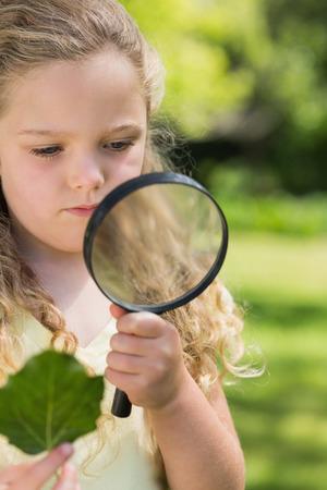 schoolkid search: Chica joven que sostiene una hoja y una lupa en el parque