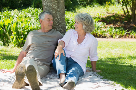 Relaxed mature couple sitting together against a tree at the park photo