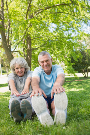 Full length portrait of a mature couple stretching hands to legs at the park photo