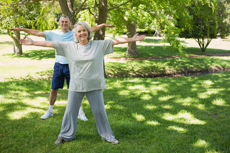 Full length portrait of a mature couple stretching hands at the park photo