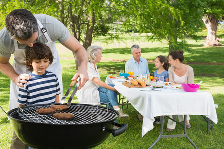 barbecue: Padre e hijo en la parrilla de la barbacoa con la familia extendida de almorzar en el parque