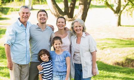 Portrait of a happy extended family standing in the park Banco de Imagens