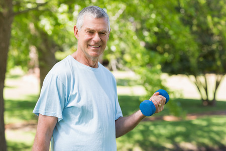 senior exercise: Portrait of a smiling mature man exercising with dumbbell at the park Stock Photo