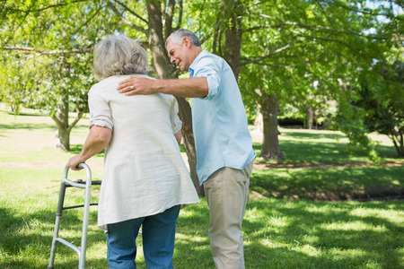 companion: Rear view of a mature man assisting woman with walker at the park Stock Photo