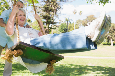 Low angle view of a mature couple at swing in the park photo