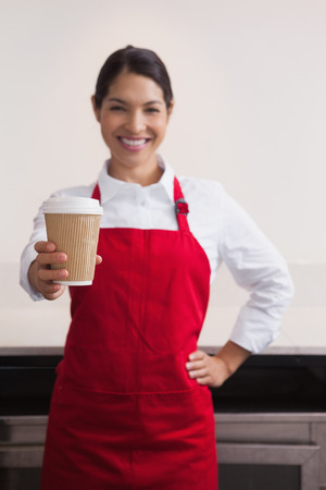 Happy young barista offering cup of coffee to go in a cafe photo