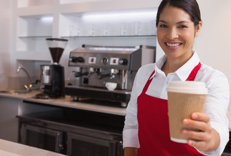 go go: Happy young barista offering cup of coffee to go smiling at camera in a cafe Stock Photo