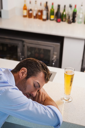 slumped: Drunk businessman sleeping beside glass of beer at the local bar