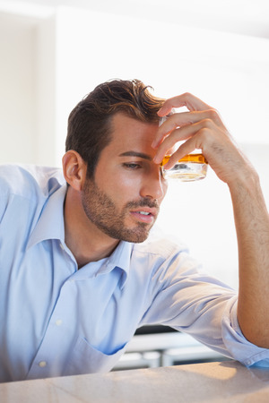 intoxicated: Drunk businessman clutching whiskey glass to forehead at the local bar