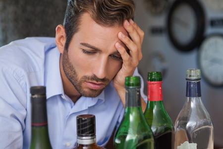 slumped: Drunk businessman looking at spirit bottles at the local bar Stock Photo