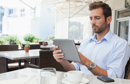 Focused young businessman working on tablet in patio of restaurant photo