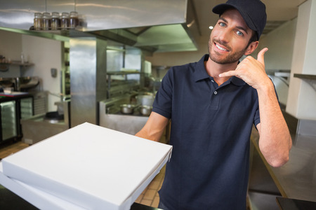 delivery man: Pizza delivery man holding pizza boxes making a phone gesture in a commercial kitchen Stock Photo