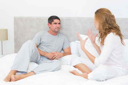 mid adult couple: Mid adult couple arguing in bed