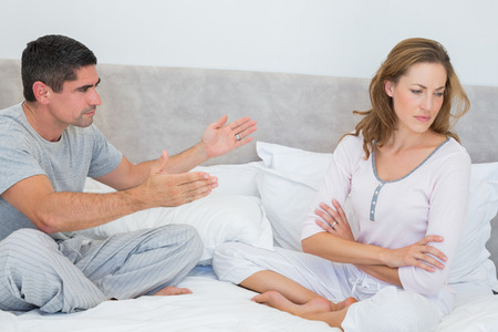 Mid adult couple fighting in bedroom photo