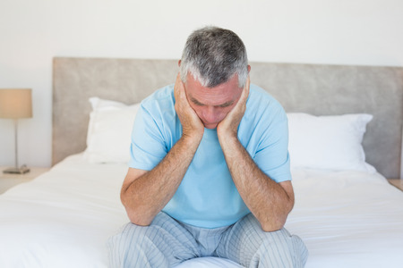 lonliness: Sad senior man with head in hands sitting on bed at home Stock Photo