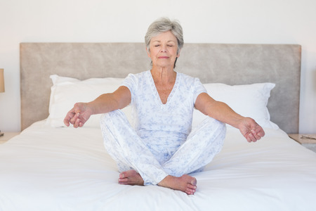 yoga pillows: Full length of senior woman meditating in bed at home Stock Photo