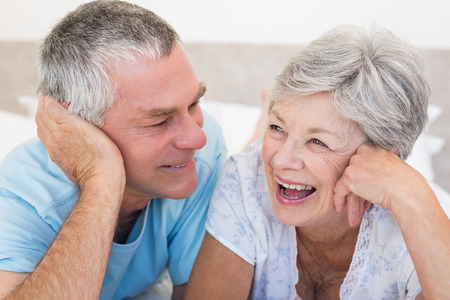 Happy senior couple lying on bed together at home photo