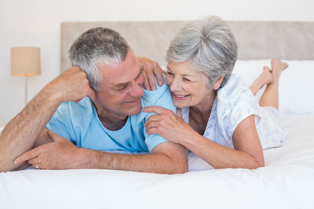 Happy senior couple smiling together while lying on bed at home photo