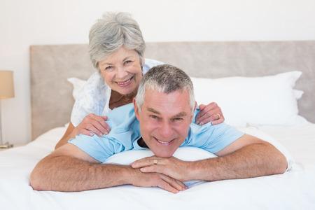 Portrait of senior woman lying on husband in bedroom photo