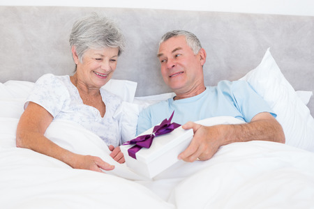 Senior man giving gift box to wife while relaxing in bed at home photo