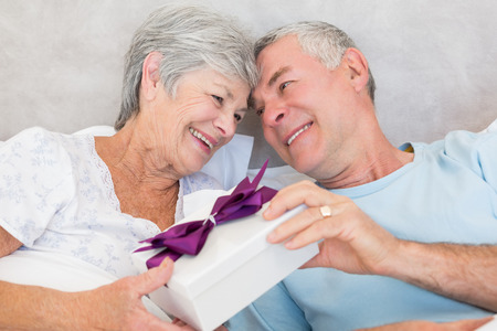Happy senior couple exchanging gift box while relaxing in bed at home photo